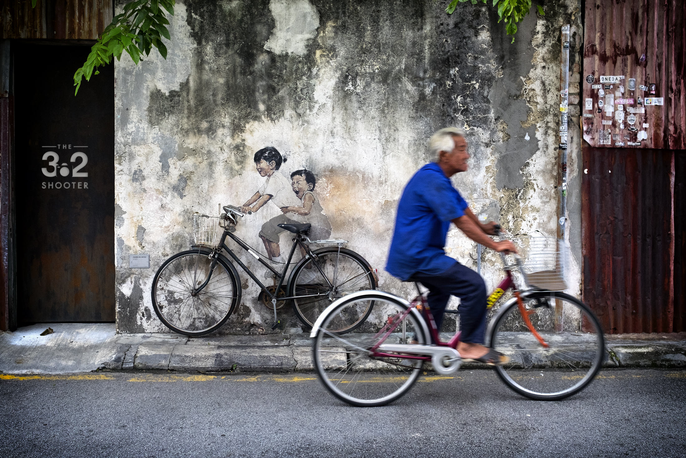Old man riding past Children on a Bicycle